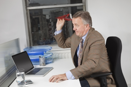 goofing: Side view of middle-aged businessman throwing paper airplane in office LANG_EVOIMAGES