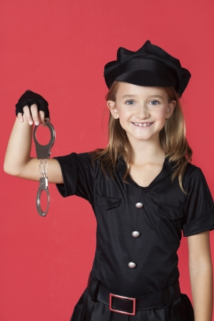 Portrait of young girl in police costume holding handcuffs against red background Stock Photo