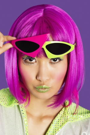 puckering lips: Portrait of young funky woman in pink wig puckering lips over purple background