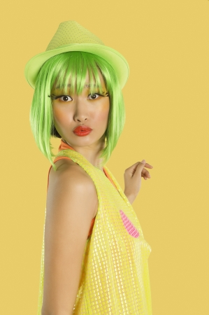 puckering lips: Portrait of funky young woman with green hair puckering her lips against yellow background