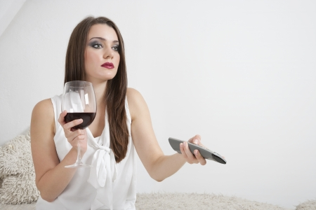 changing channels: Young woman holding wineglass while changing channels with remote control LANG_EVOIMAGES