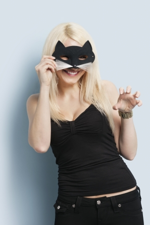 clawing: Portrait of young woman wearing a cat mask over light blue background LANG_EVOIMAGES