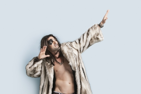 coats of arms: Young man in fur coat looking up with arms raised against light blue background
