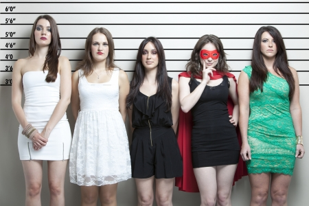 Young woman in superhero costume with friends in a police lineup 版權商用圖片