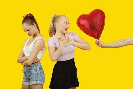 gifting: La mano del hombre gifting globo en forma de coraz�n para la mujer sorprendida con el amigo sentirse excluido de pie detr�s LANG_EVOIMAGES