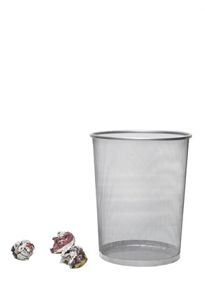 wastebasket: Crumpled papers next to empty wastebasket over white background