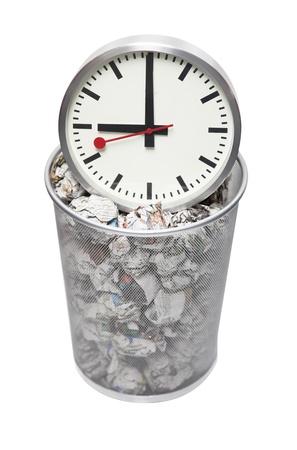 wastebasket: Clock in wastebasket full of crumpled paper over white background