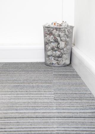 wastebasket: Wastebasket full of crumpled paper in corner on carpet floor in room LANG_EVOIMAGES