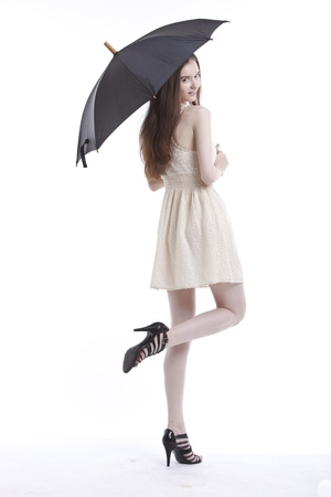 mini umbrella: Portrait of beautiful young woman in dress with umbrella against white background