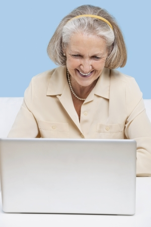 videoconferencing: Cheerful senior woman using laptop for video calling