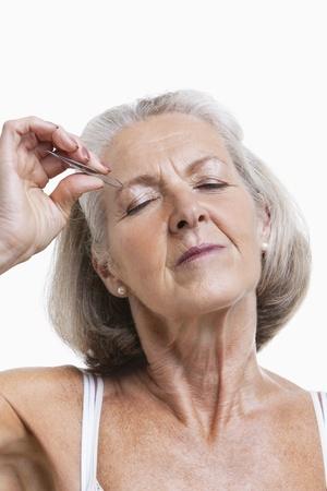 tweezing: Senior woman tweezing eyebrows against white background