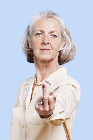 middle finger: Senior woman in casuals making rebellious hand gesture against blue background