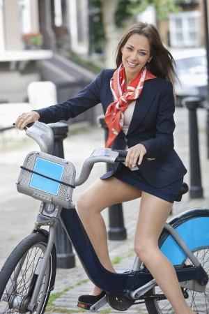transportation: Portrait of happy young businesswoman with bicycle