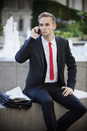 business: Young businessman sitting on platform while using cell phone LANG_EVOIMAGES