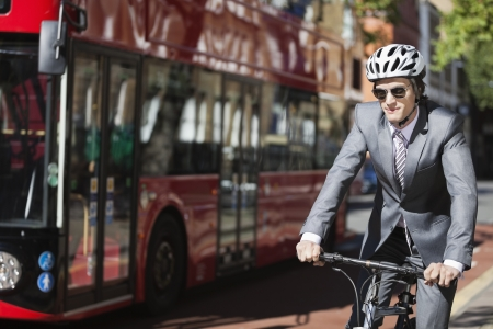 transportation: Young businessman riding bicycle by bus on street LANG_EVOIMAGES