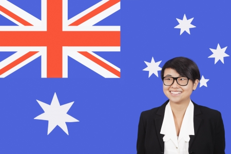 australian ethnicity: Portrait of young businesswoman smiling over Australian flag