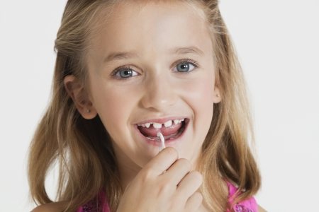 flossing: Portrait of young girl flossing teeth against gray background LANG_EVOIMAGES
