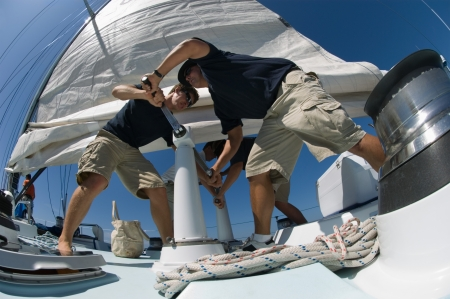 Sailors operating windlass on yacht low angle view