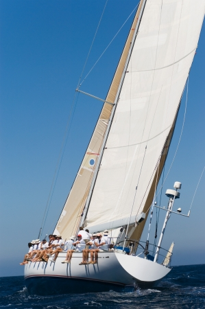 Crew sitting on Side of sailboat side view