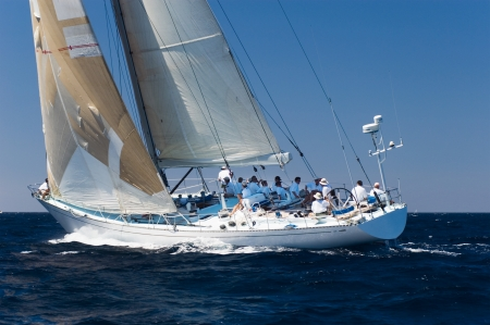 Crew sitting on sailboat on ocean