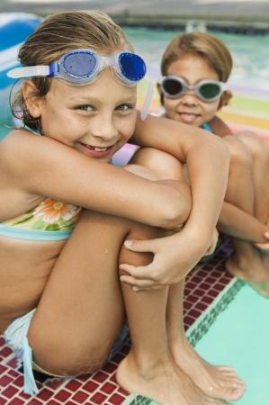 e9a1369e #21008813 - Dos chicas (7-9) que se sienta en el borde de la piscina  retrato.