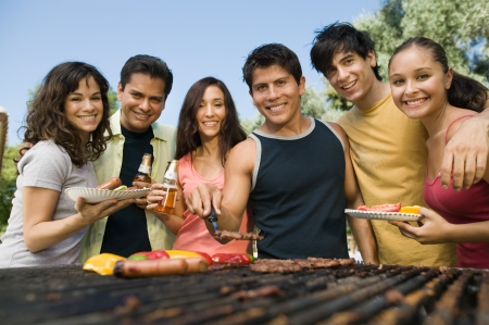 tog: Group of young people around outdoor grill.