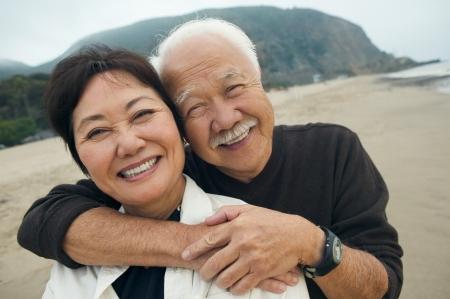 hugging couple: Mature couple embracing on beach (close-up) (portrait) LANG_EVOIMAGES