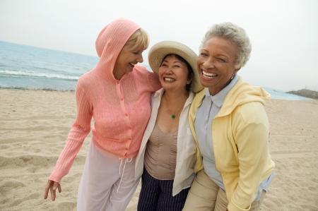 50s women: Female friends walking side by side on beach