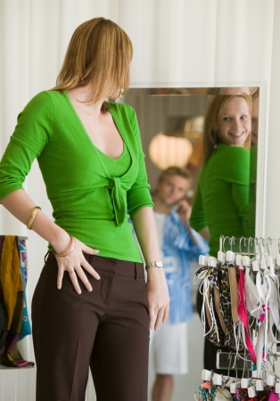 one person with others: Woman Looking at Clothing in Store Mirror