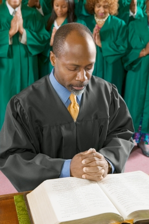 Preacher by altar in church Bowing Head in Prayer high angle view