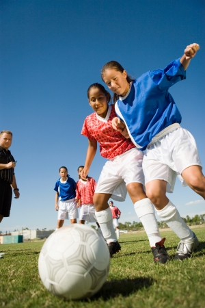 view girl: Girls (13-17) playing soccer low angle view LANG_EVOIMAGES