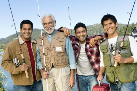 mixed age range: Hombre de mediana edad con tres hijos con ca�as de pescar sonriendo (vertical) LANG_EVOIMAGES