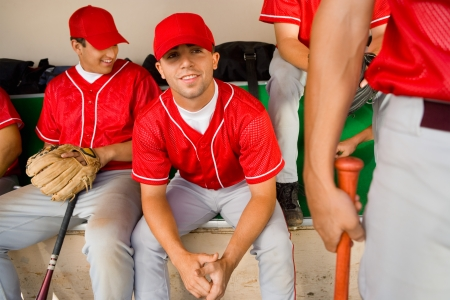 Baseball team-mates sitting in dugout