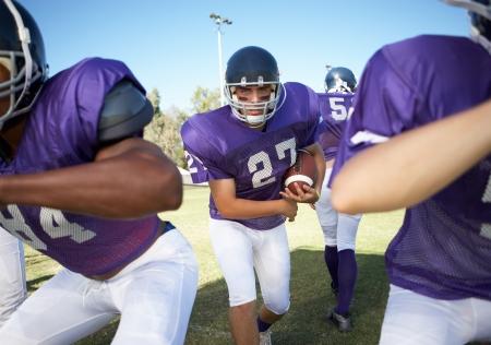 linemen: Football player running behind linemen on field LANG_EVOIMAGES