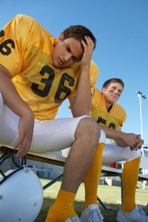 anguished: Two football players sitting on bench low angle view