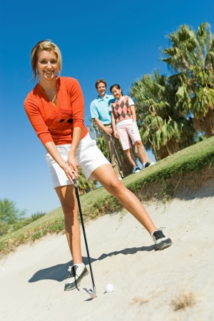 one person with others: Female golfer hitting ball from sand trap LANG_EVOIMAGES