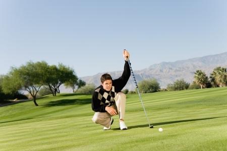 lining up: Golfer lining up putt LANG_EVOIMAGES