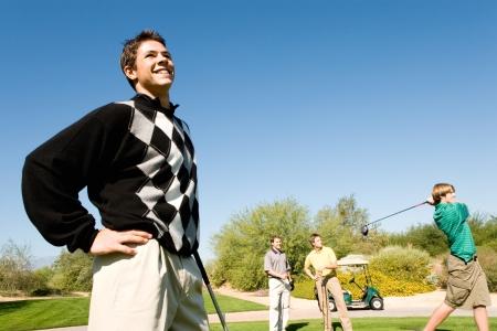 golf swing: Golfer watching other golfer teeing off