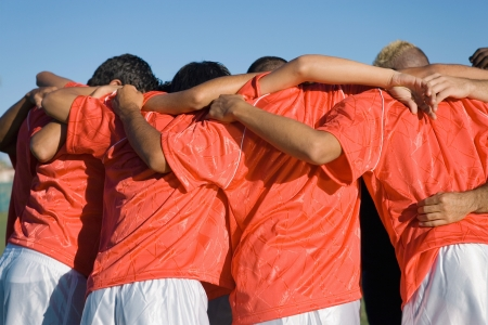 team mate: Soccer team in huddle back view