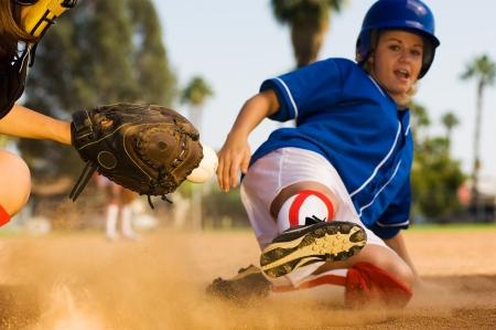 Softball player sliding into home plate Stock Photo