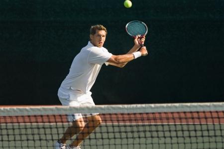 backhand: Jugador de tenis en cuclillas en la cancha de tenis que golpea rev�s sobre la red