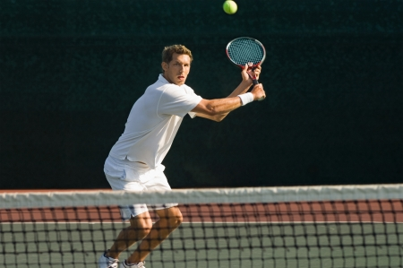 tennis player: Tennis Player squatting on tennis court Hitting Backhand over net LANG_EVOIMAGES