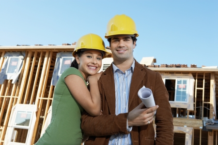 two people with others: Couple in front of houses being built LANG_EVOIMAGES