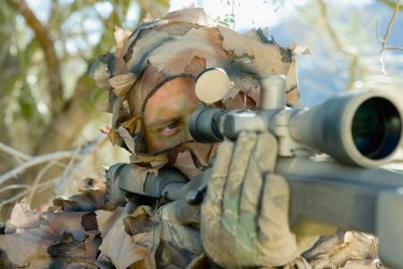 gunsight: Soldier aiming through gunsight outdoors (close-up)