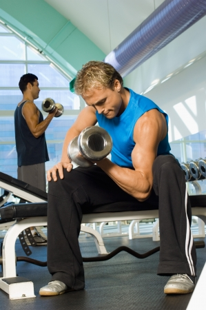 one person with others: Man using dumbbell in gymnasium