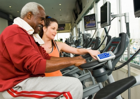 active seniors: Woman assisting man on exercise bike in gymnasium LANG_EVOIMAGES