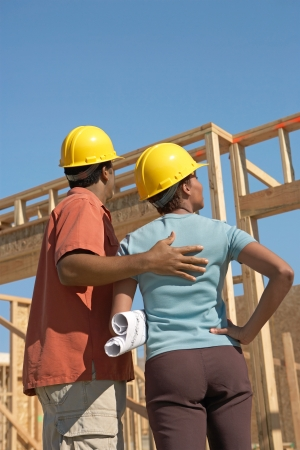 hard hats: Couple in hard hats on building site back view LANG_EVOIMAGES