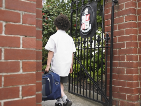 back gate: Elementary schoolboy walking through school gate back view LANG_EVOIMAGES