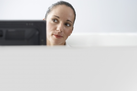 office cubicle: Female office worker sitting behind monitor in office cubicle