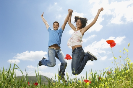 Young couple jumping for joy in mountain meadow portrait low angle view